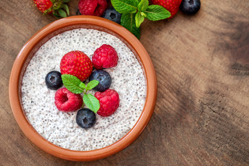 Chia. Superfoods breakfast with Chia seed pudding and  berries in a bowl over wooden rustic background. Health concept, omega 3 product. Top view, flat lay.