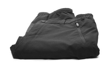 Folded pair of black sports, trekking pants isolated on white background