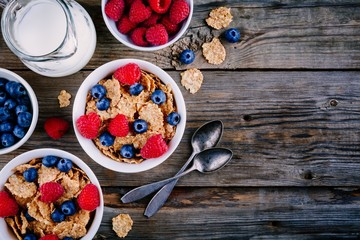 A healthy breakfast bowl. Whole grain cereal with fresh blueberries and raspberries on wooden background. Top view