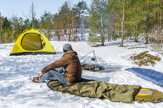 Climber arranges the sleeping pad in the bag near yellow tent in winter