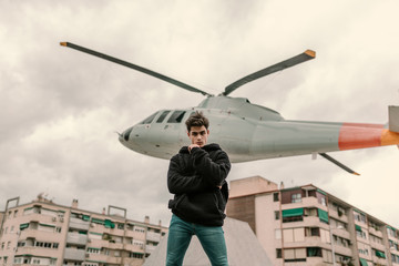 Young man standing at helicopter