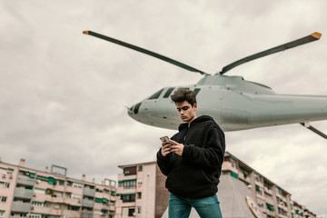 Young man standing at helicopter with smartphone