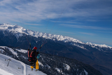 The snowboarders, skiers in action at the mountains.Paraglider with an instructor.