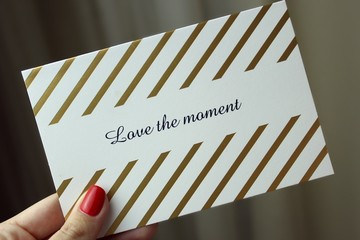 "A girl holding a ""Love the moment"" greeting card"