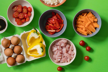 Ingredients for the preparation of traditional fried rice in Thai: white rice, cherry tomatoes, pepper, soy sauce, eggs, chicken meat, carrots. Food on a green background. recipe Asian.