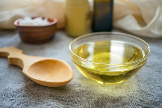 Liquid coconut MCT oil in round glass bowl with wooden spoon and bottles. Health Benefits of MCT Oil. Triglycerides, a form of saturated fatty acid