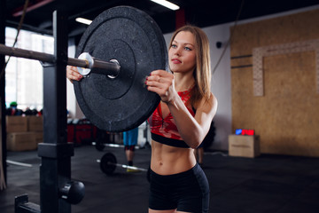 Picture of athlete woman in sports clothes with barbell