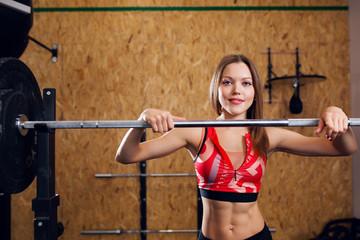 Image of young athlete in sports clothes with barbell