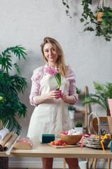 Image of florist woman in apron at room with flowers