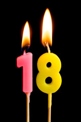Burning candles in the form of 18 eighteen figures (numbers, dates) for cake isolated on black background. The concept of celebrating a birthday, anniversary, important date, holiday, table setting