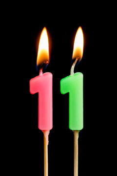 Burning candles in the form of 11 eleven figures (numbers, dates) for cake isolated on black background. The concept of celebrating a birthday, anniversary, important date, holiday, table setting