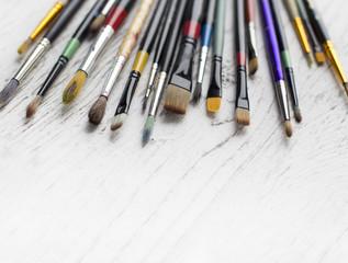 Artist brushes on white wooden background