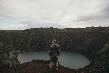 Man on hill looking at lake