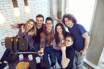 A group of friends are photographed on a phone indoors.