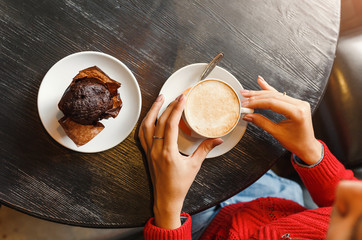Young woman drinking coffee and eating a delicious muffin cake in retro cafe, breakfast and good morning concept