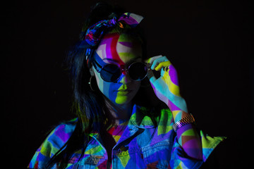 Pretty woman with colorful light on face and sunglasses