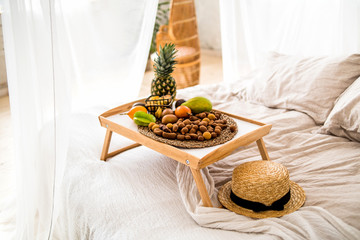 tropical fruits on the tray on the bed
