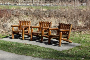 The wooden chairs in the park on a sunny day.