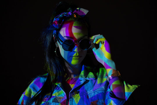 Woman in sunglasses with geometric colorful light on face