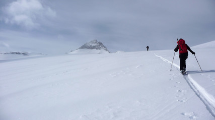 two backcountry skiers on a tour in the Austrian Alps and putting in new tracks on their way to the summit