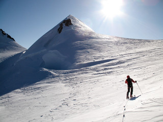 male back country skier on a ski tou on his way to a high alpine summit in the Monte Rosa mountains on a huge glacier