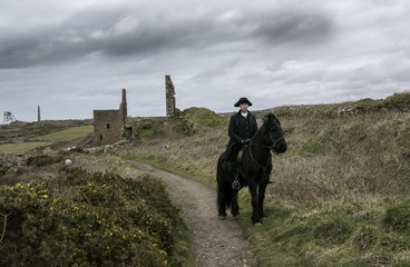 Handsome Male Horse Rider Regency 18th Century Poldark Costume with tin mine ruins and Cornish countryside in background