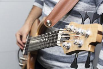 Closeup photo of bass guitar player hands, soft selective focus, live music theme