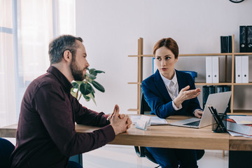 businesswoman and client discussing contract at workplace in office
