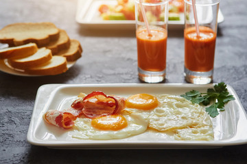 Daily Breakfast. Fried egg with bacon, carrot juice, vegetable salad, bread. On dark stone background