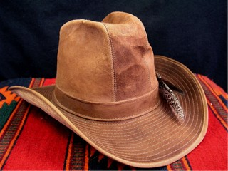 Isolated brown explorer or cowboy hat with feathers on Native American style blanket