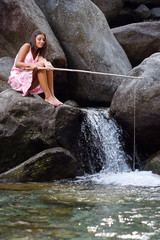 Girl seated on a rock fishing