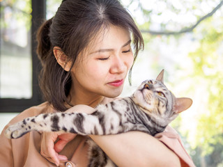 Portrait of a beautiful young Chinese girl hold a bengal cat in arms with smile,  full of love, pet lover concept.