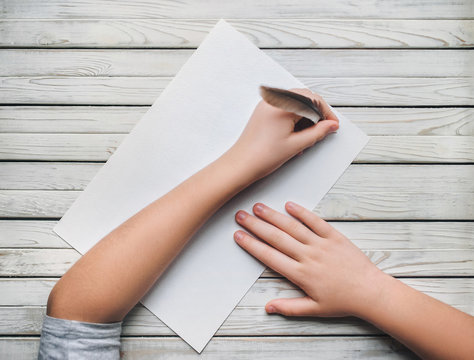 Left-handed. A girl writes with a pen on a white sheet of paper. The young poet writes poetry. World Poetry Day.