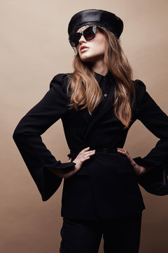 Fashion portrait of beautiful young woman in black flared jacket, black leather beret cap and dark sunglasses with veil. Standing with hands on waist