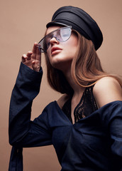 Fashion portrait of beautiful young woman in black leather beret cap, denim blouse and blue retro sunglasses