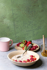 Sweet rice porridge pudding in ceramic plate with berries strawberry and raspberry, walnuts, honey and mug of milk on grey kitchen table with green wall as background.