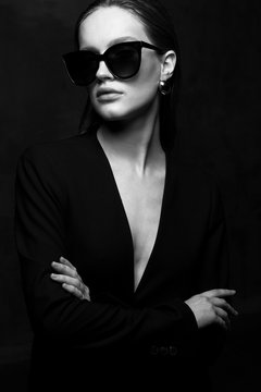 Sexy elegant black and white portrait of young beautiful woman in black deep v neck jacket and dark sunglasses