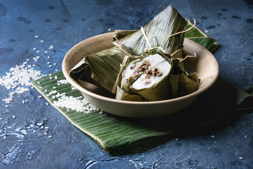 Asian rice piramidal steamed dumplings from rice tapioca flour with meat filling in banana leaves served in ceramic bowlwith rice above over blue texture background. Close up, space.