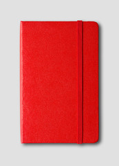 Red closed notebook isolated on grey
