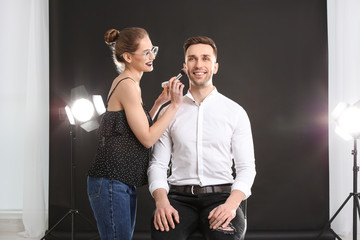 Professional makeup artist working with  young man in photo studio