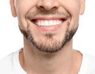 Young man with beautiful smile on white background. Teeth whitening