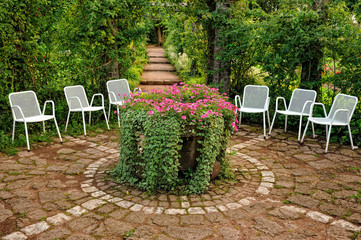 Resting place in the garden. Metallic white chairs for resting in the garden.