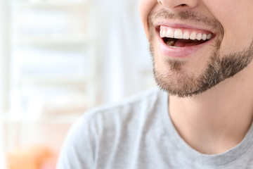 Young man with beautiful smile indoors. Teeth whitening