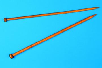 Wooden knitting needles on blue background.