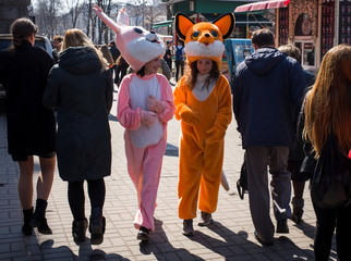 Women dressed as a rabbit and a fox, who pose for pictures with tourists, walk in central Kiev