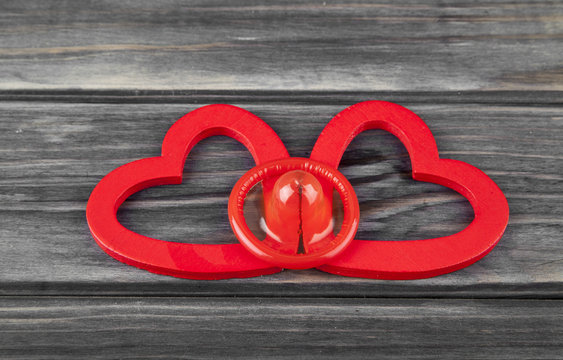 red hearts and condom on a wooden background