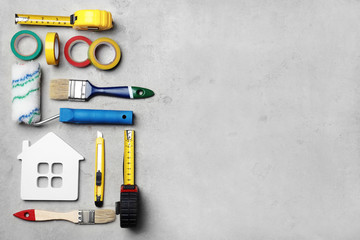 Set of decorator's tools on grey background, flat lay