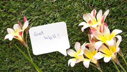 Note in shape of a chat bubble, with words Get Well! and flowers on green grass.