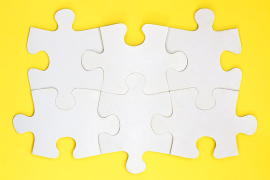 Group of six white paper jigsaw puzzles. Connected blank puzzle pieces on a yellow background. concept of teamwork. unity, partnership, cooperation and teamwork.