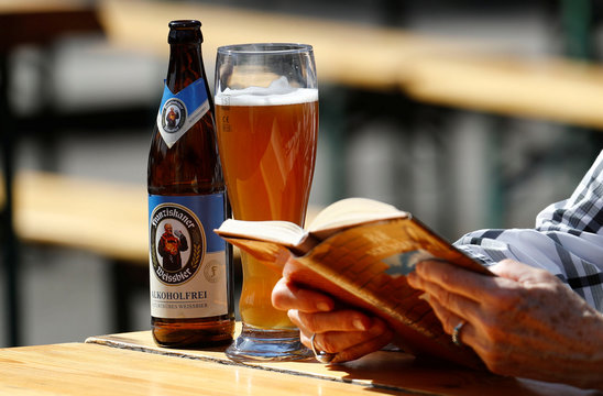 A woman reads a book next to a glass of German alcohol free Weizen beer at a beer garden in Berlin